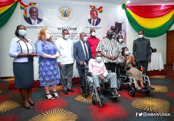 Persons from the Ministry of Ghana standing for a photo with Persons in a wheelchair