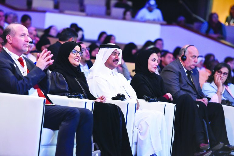 Group of persons seated int he front row of an event.