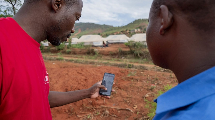 CBM Zimbabwe Emergency Response Team member Allen Chaitezvi and Local Disabled Persons Committee chair Tapiwa Sigauke review the Humanitarian Hands-on Tool (HHoT) app at an Internally Displaced Persons (IDP) camp in Chimanimani, Zimbabwe, on November 24, 2019. Tapiwa lost his arm in a traffic accident. © CBM/Hayduk