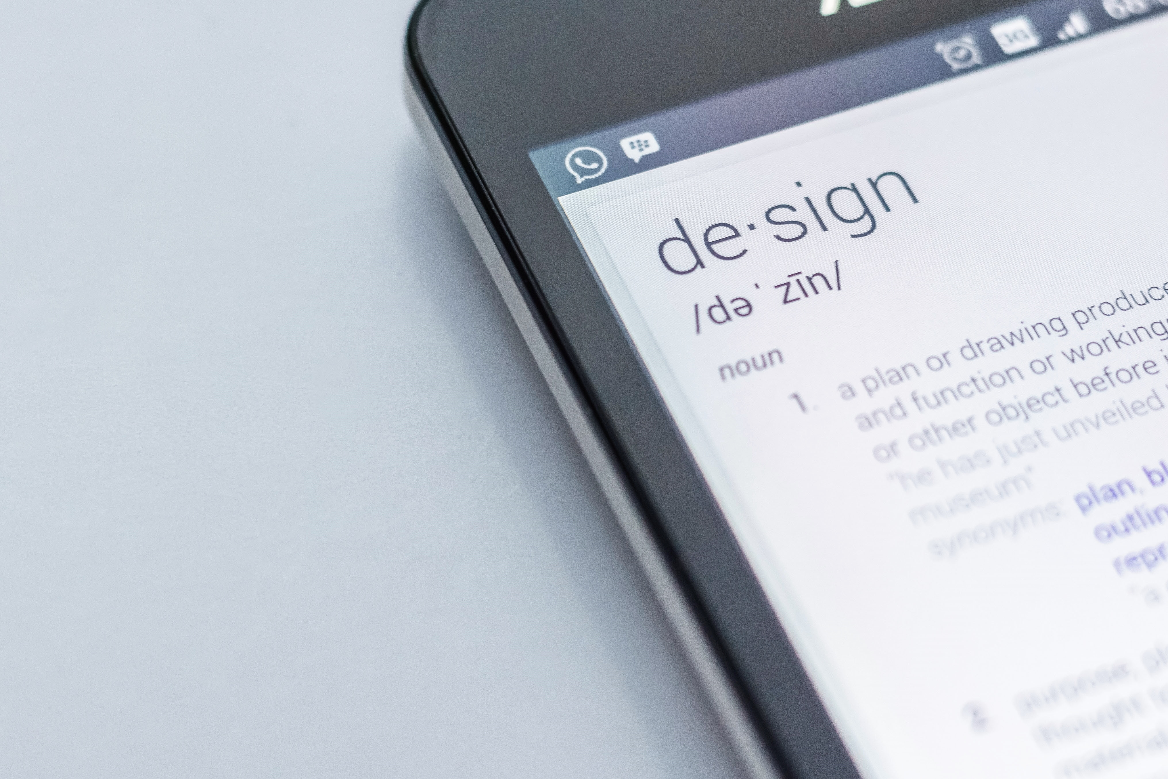 Close-up partial view of an iPhone with the dictionary definition of design on the screen