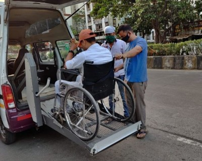 Person on a wheelchair entering a waiting van