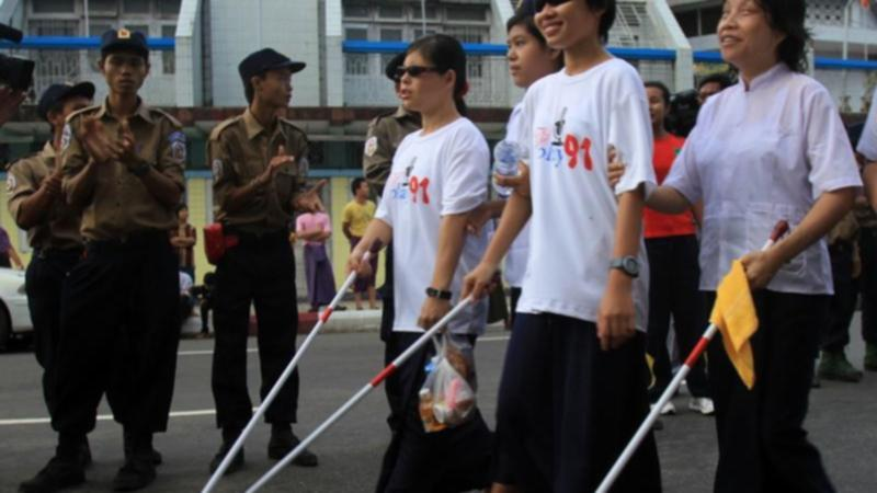 Persons with visual impairment walking on the street with their canes.