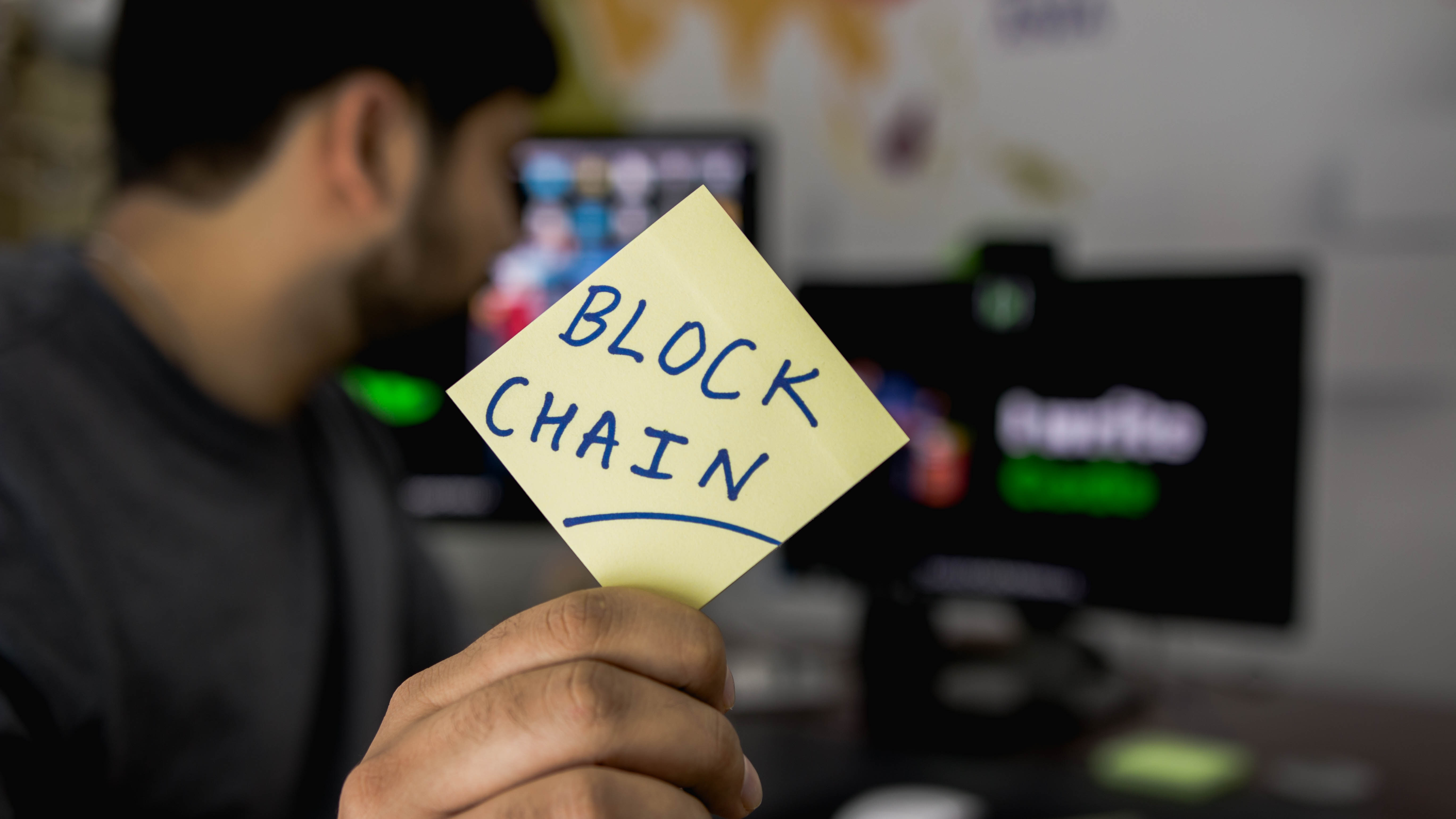Blurred man sits in front of computer screens holding out a sticky note to the side. In focus, it reads 'block chain'