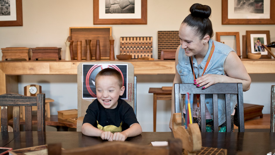 Mark Ovington, 5, tests out the chair designed for him through Adaptive Design Greater Philadelphia as his mother, Andrea Krajci, watches. Kim Singleton of Temple's Institute on Disabilities later put finishing touches on the chair. (Photo: Ryan S. Brandenberg)