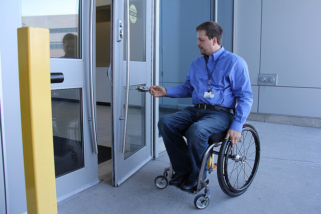 Accessibility Assessor during an assessment - checking the weight of doors.