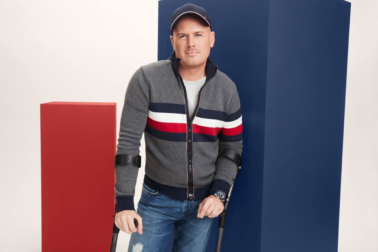 Man with arm braces wearing the Tommy Adaptive Adaptive Clothing Line