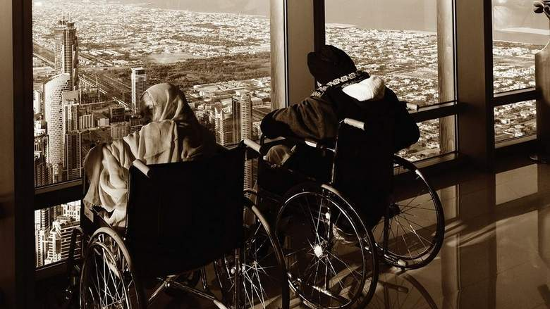 Two people seated in wheelchairs overlooking a view of the city of Dubai