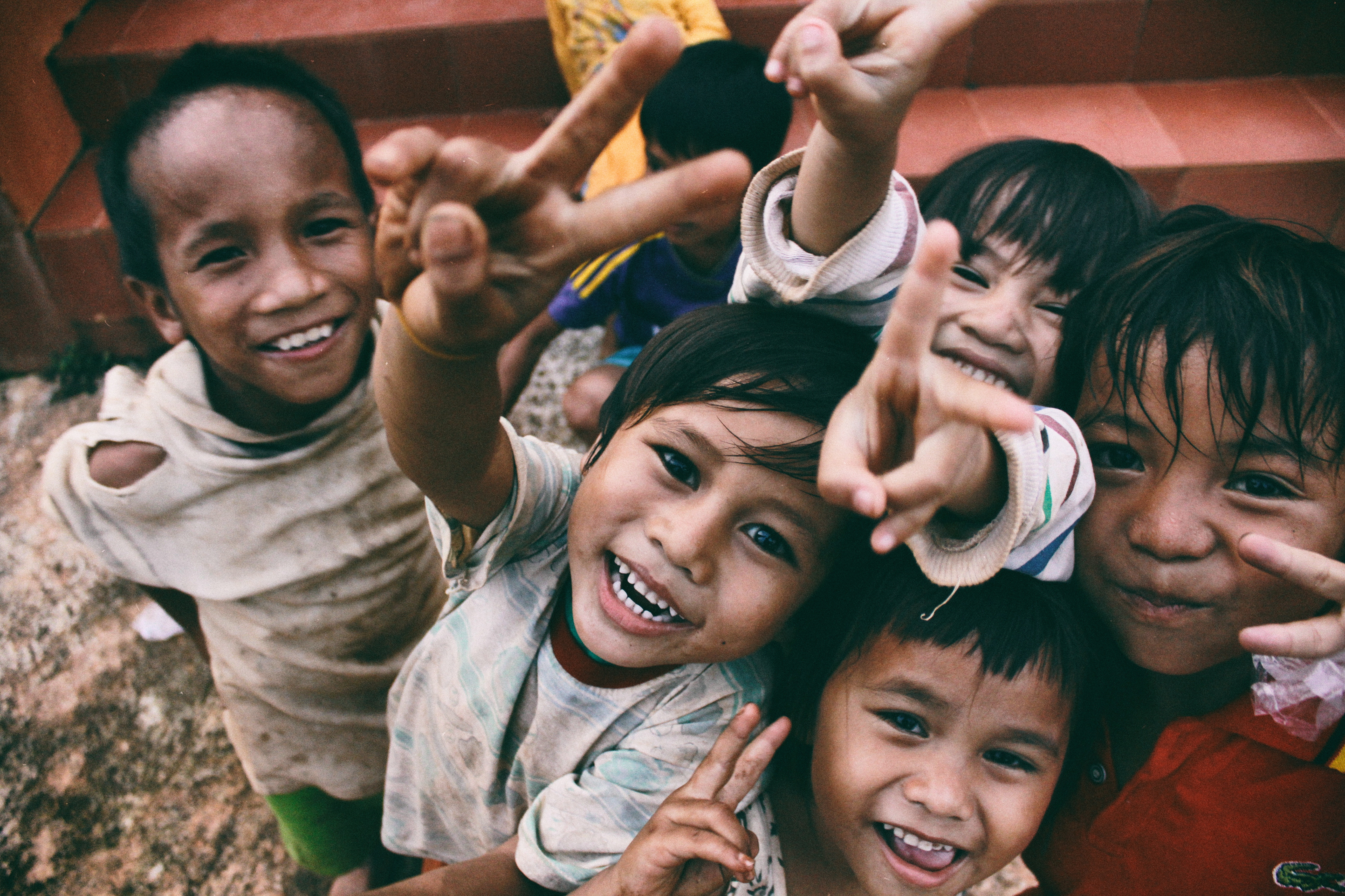 A group of children smiling for the camera and making peace signs with their fingers.