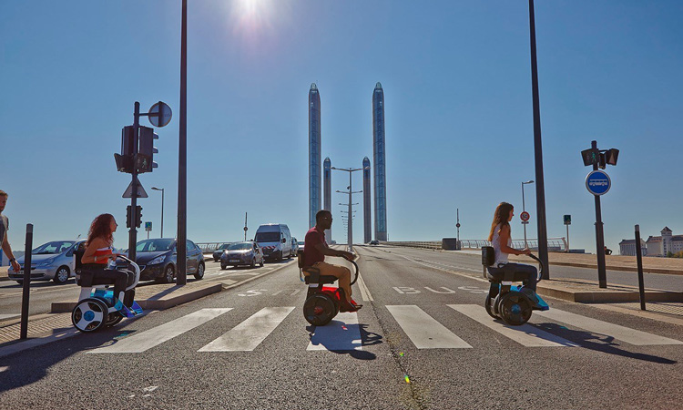 Two persons on robotic scooters crossing the road