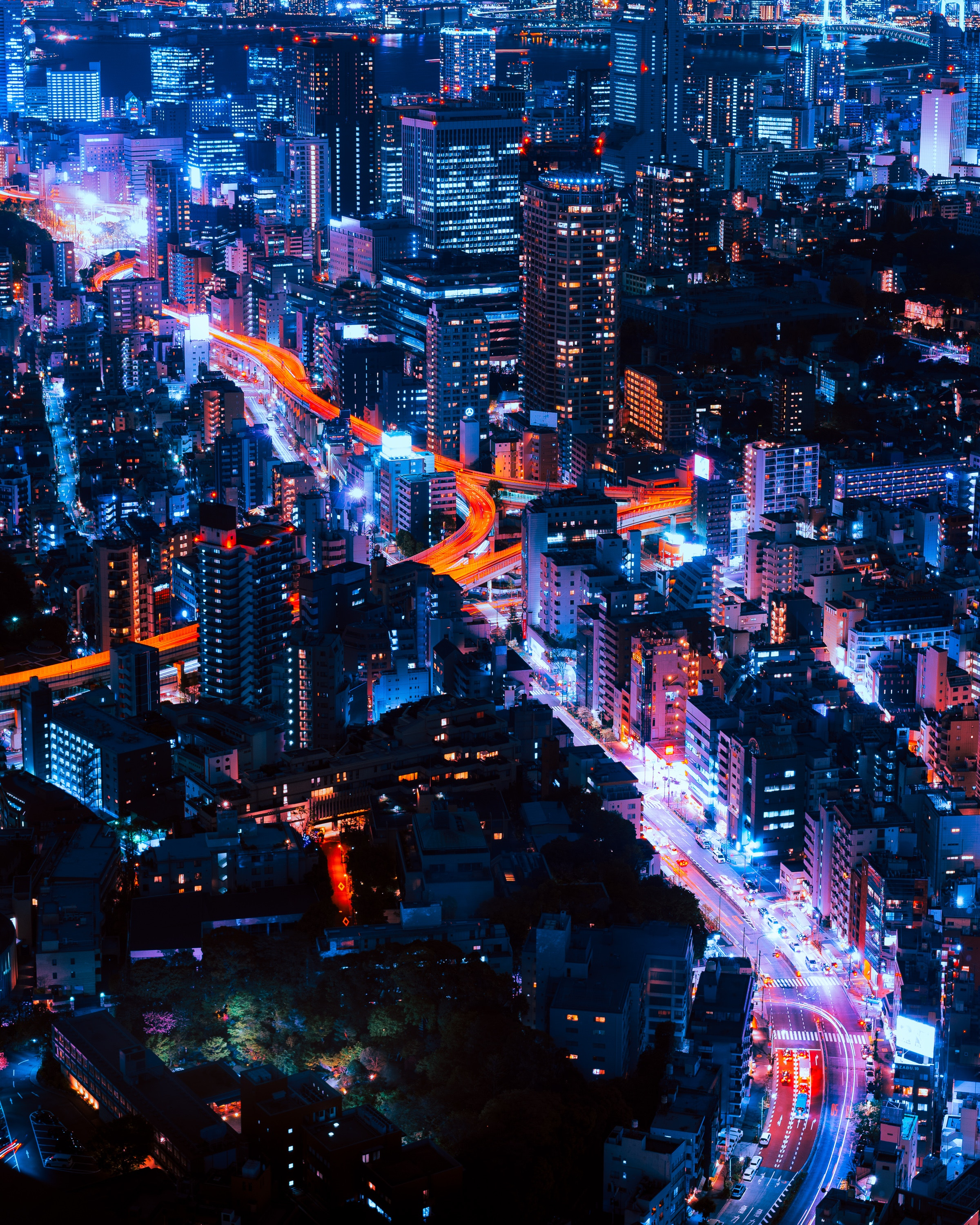 Skyline view of Tokyo with orange and blue lights illuminating its streets