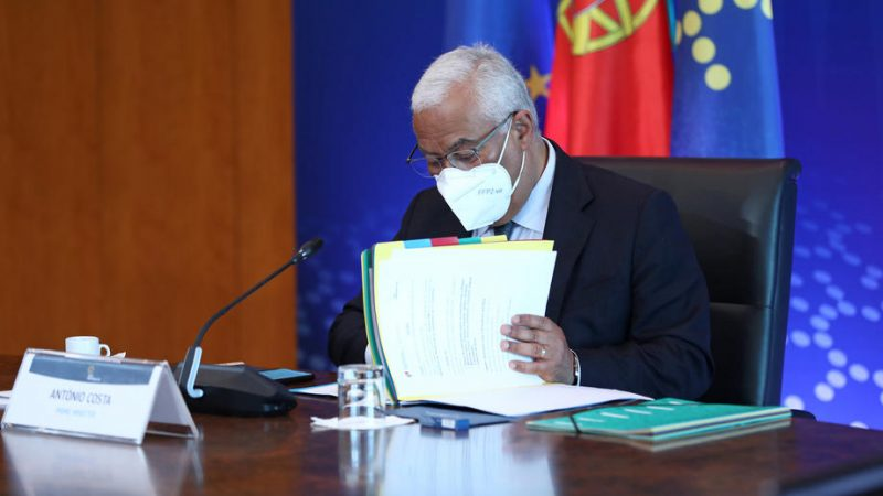 photo of Portuguese Prime Minister Antonio Costa wearing a mask and going over some official documents