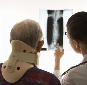 A man wearing a neck brace looks at an X-Ray with his doctor