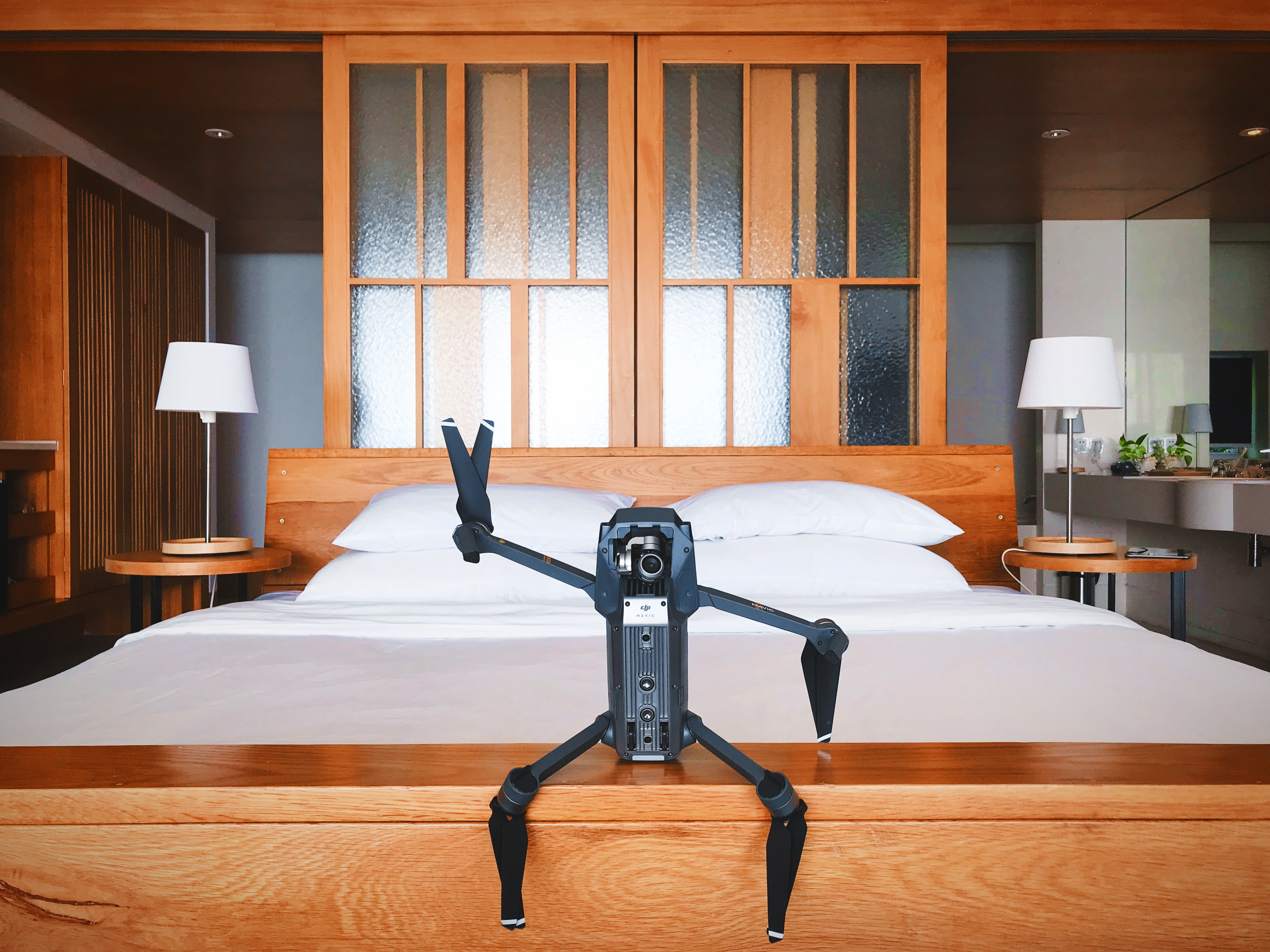 Personal home robot waving and sitting at the foot of a bed on it's wooden frame at the foot of a