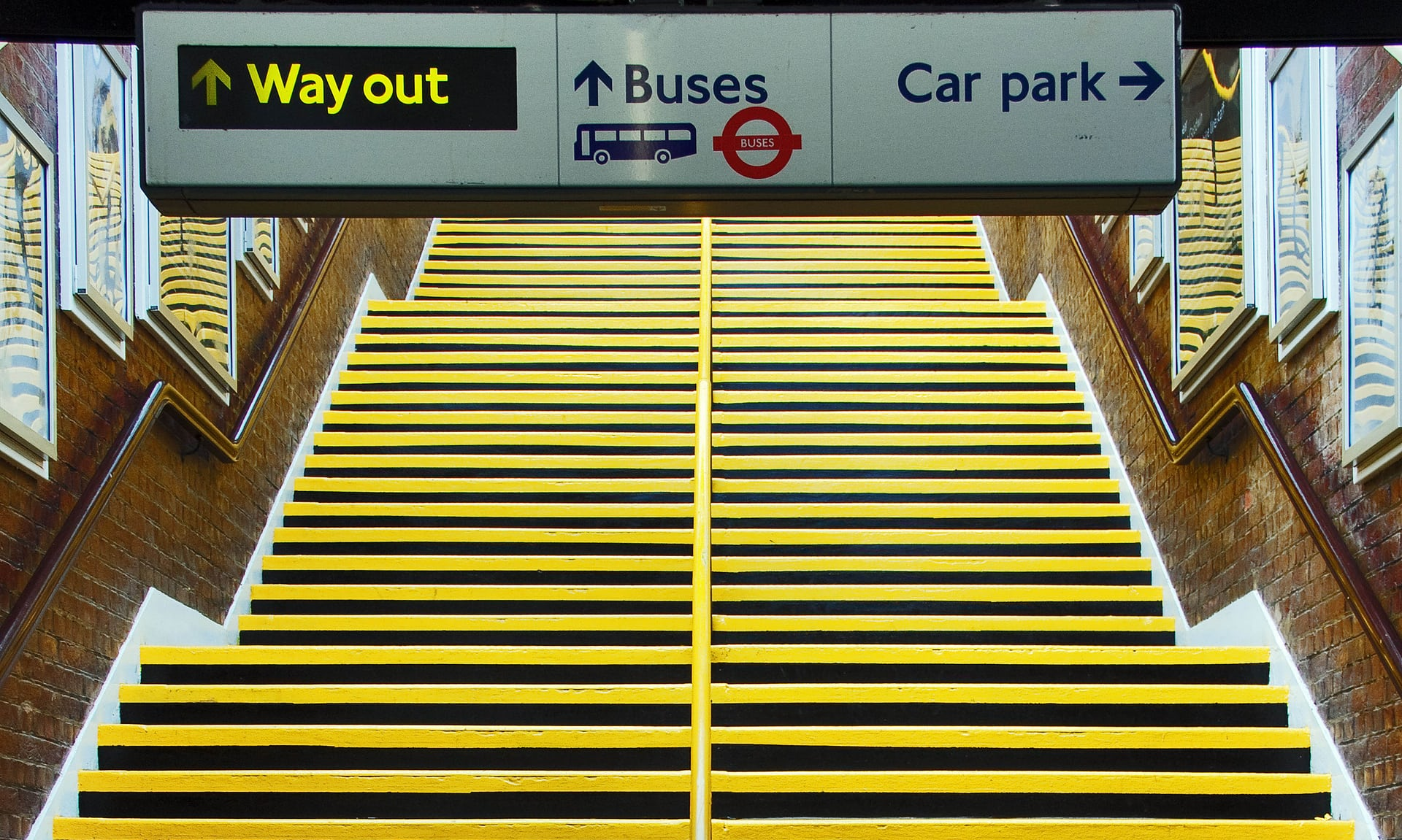 Photo of the subway stairs with signs indicating the way out, buses and carpark