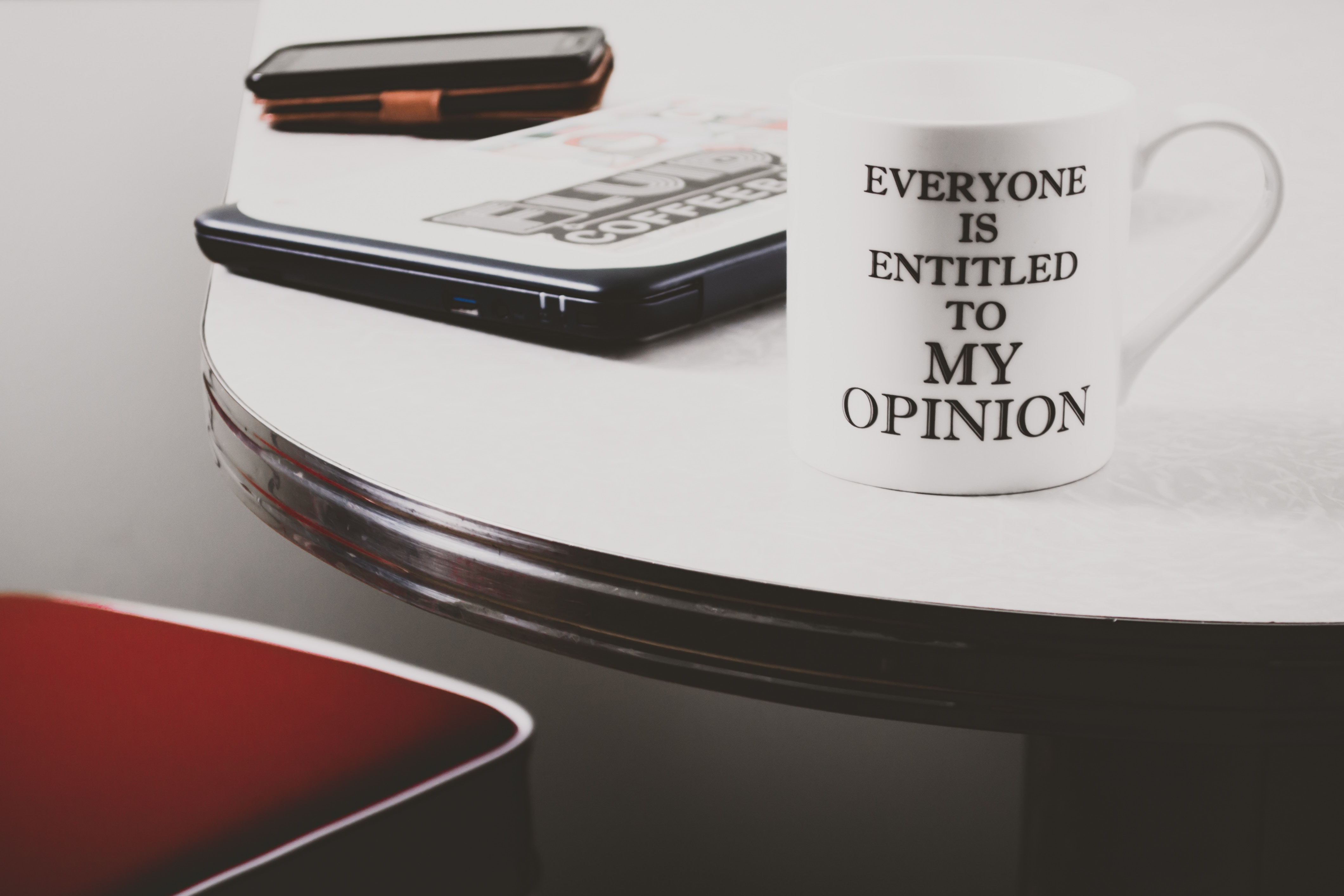 ceramic mug that reads 'Everyone is entitled to my opinion' on a desk next to a laptop