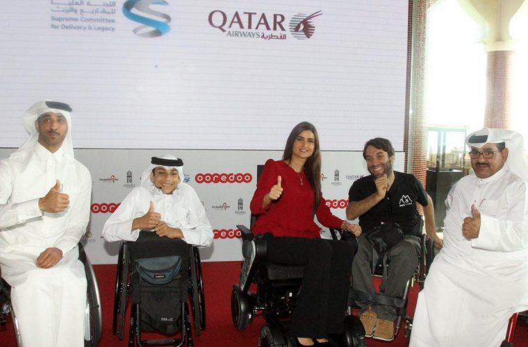 Four men and one woman in a wheelchair giving a thumbs up sign