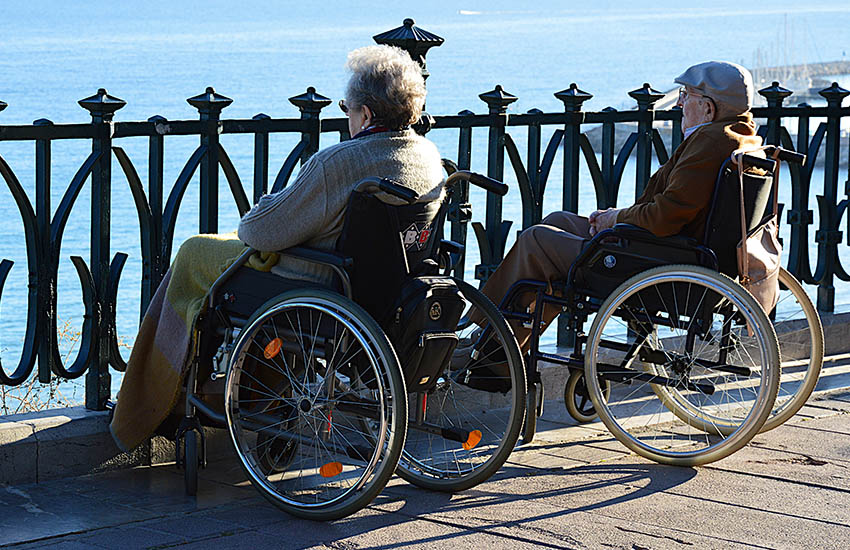 Two persons seated in a wheelchair looking out into a water body