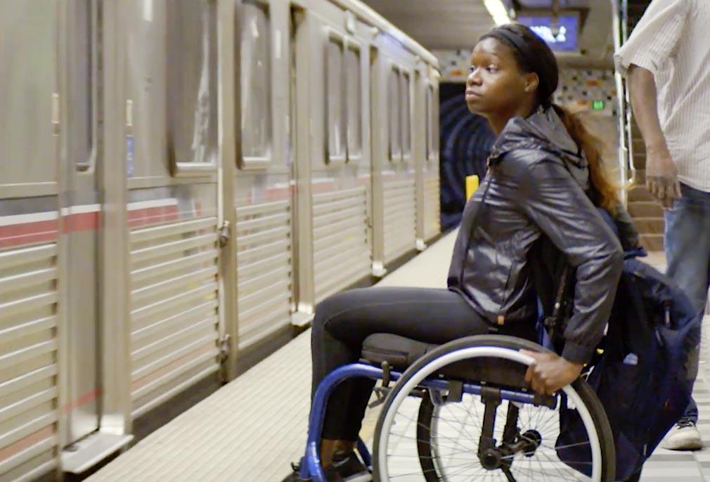 Woman in wheelchair on subway platform